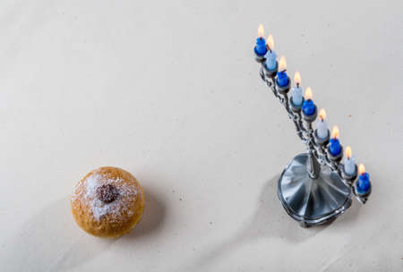 Hanukkah menorah, candle holder for nine candles and sufganiyah - traditional deep-fried donut for Jewish holiday of Hanukkah