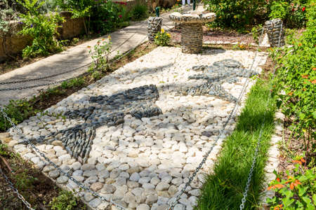 SEA OF GALILEE, ISRAEL - MAY 15: Stone sculpture composition - two fish and five loaves of bread in landscape park, Church of Mount of Beatitudes at the Sea of Galilee, Israel on May 15, 2017 Editorial