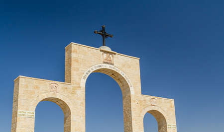Arched entrance with cross to the canyon of the monastery of Saint George of Choziba near Jericho in Judaean desert, Israel