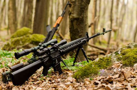 Sniper rifle on bipod on forest background