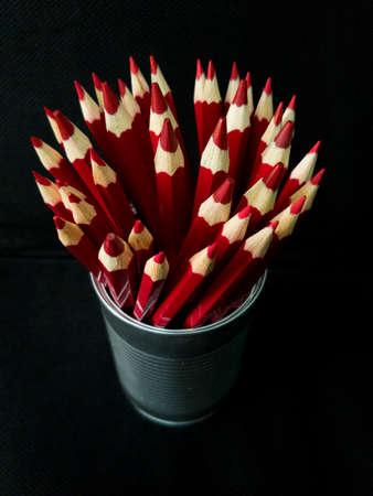 variegated: Red pencils on black background