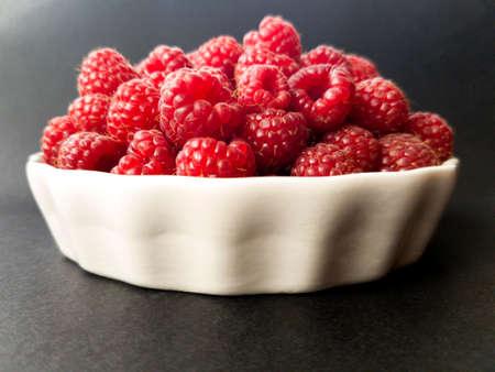 Raspberries in a white bowl Stock Photo