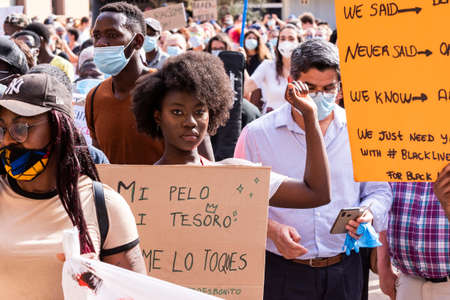 Palma de Mallorca, Spain - June 07 2020: Girl raising the fist and holding a banner in a peaceful protest. Written in spanish: