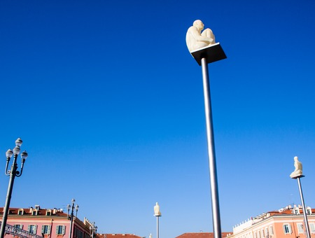 statues of a crouched man on a top of a pole in Nice France Banque d'images - 111062410