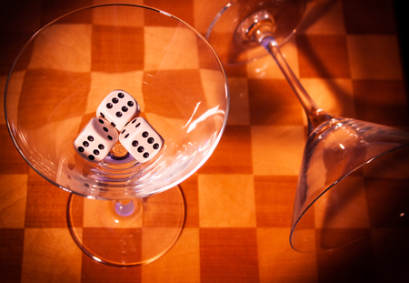 two glasses on a chessboard with three dices Banque d'images - 111062638