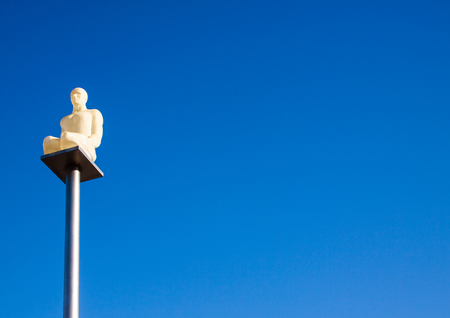 statue of a crouched man on a top of a pole in Nice France Banque d'images - 118508947