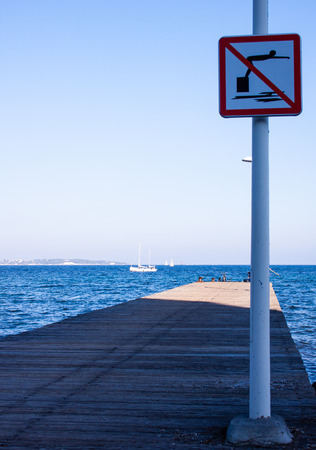 a pier with a sign post for dive interdiction close to Cannes Banque d'images - 118508982