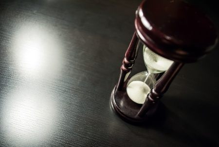 hour glasses: old hourglass stand on a dark wooden table Stock Photo