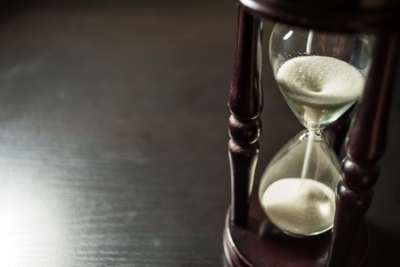 the hours: old hourglass stand on a dark wooden table  view from below