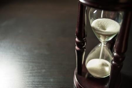 reloj de arena: soporte de reloj de arena de edad en una vista de tabla de madera oscura de abajo Foto de archivo