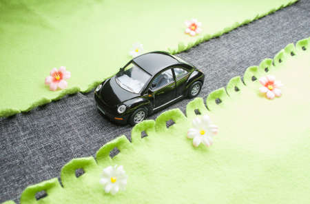Toy car that travels on the road  The road and the grass made ​​out of fabric  photo