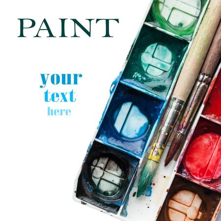 Palette of watercolor paints with paintbrushes and space for your text. photo