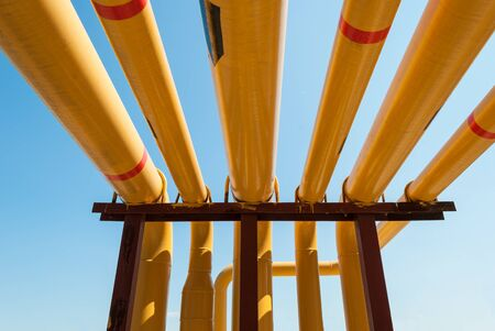 oil and gas industry: Several yellow pipelines against blue sky inside of a modern industrial power plant
