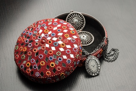 Old indian jewelery box with the earrings and pendant on a wooden background. photo