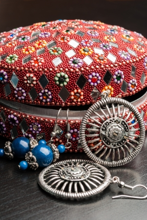 Old indian jewelery box with the closeup earrings on a wooden background. Vertical composition. photo