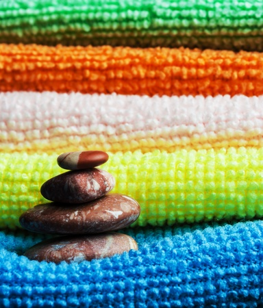 Closeup stack of colorful towels and tower of stones. Stock Photo