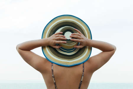 mujer mirando el horizonte: Young woman in straw hat standing by the sea and looking to horizon