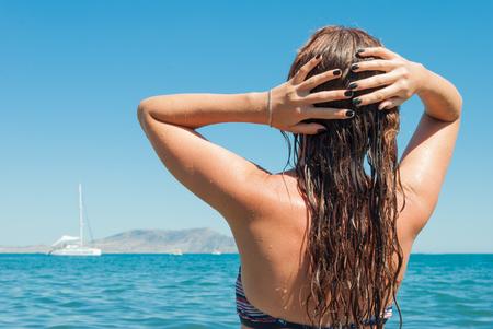 wet bikini: Beautiful young woman in bikini on beach with wet hair Stock Photo