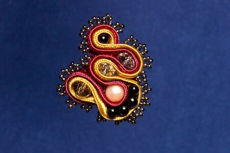 Soutache modern brooch with beads on violet background Stock Photo - 12929194