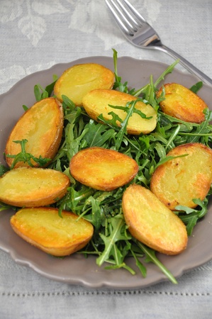 potato wedges: Fresh rucola leaves with potato wedges Stock Photo