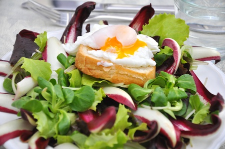Salad with poached, soft egg photo
