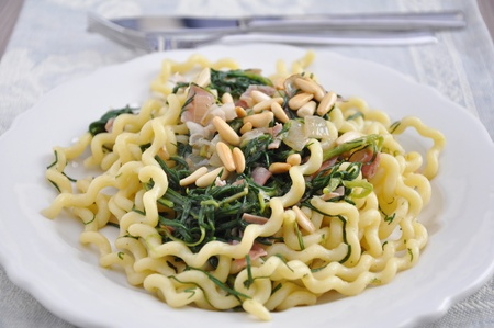 Pasta with pine nuts, bacon and spinach photo