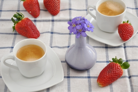Coffee cup with strawberries and flowers photo