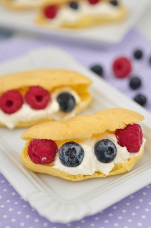 Eclair with Cream and fresh Berries Stock Photo