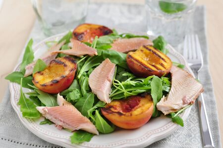 Salad with grilled peach and smoked trout photo