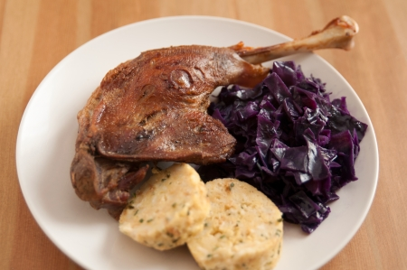 Roasted goose leg with braised red cabbage and dumplings Stock Photo