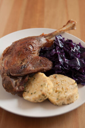 Roasted goose leg with braised red cabbage and dumplings photo