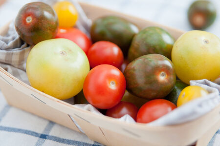 Many different tomato breeds in a wooden box  photo