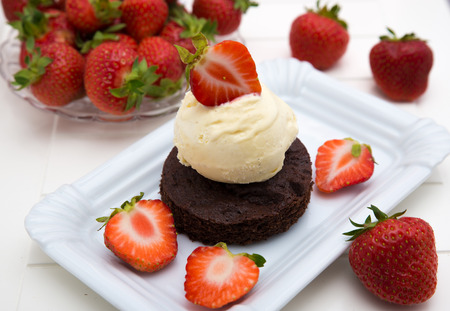 Brownie with vanilla ice cream and strawberries photo
