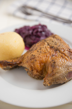 Roast duck legs with potato dumplings and red cabbage photo