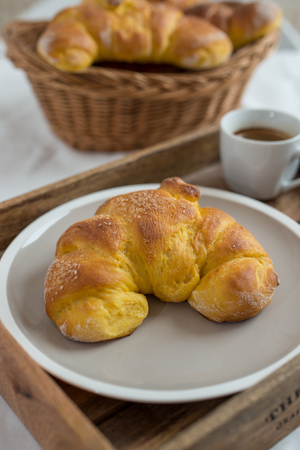 Homemade croissant served with black coffee and jam