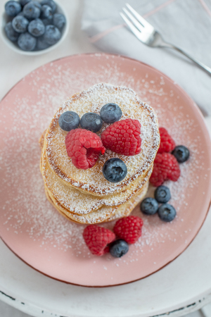 Sugar-powdered pancakes with raspberries and blueberries Foto de archivo