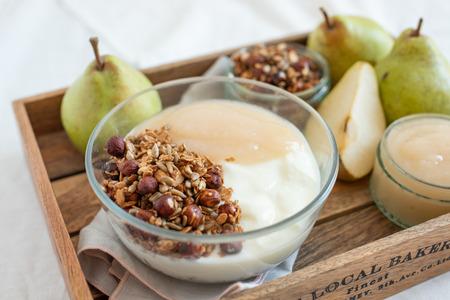 A tray of healthy breakfast - pear, yogurt, muesli