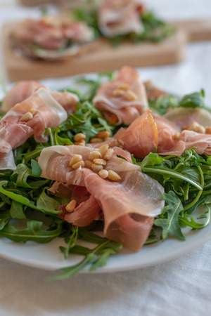 Healthy salad with prosciutto, tomato and green leaves Фото со стока