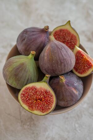 Whole figs and sliced figs in ceramic bowl.