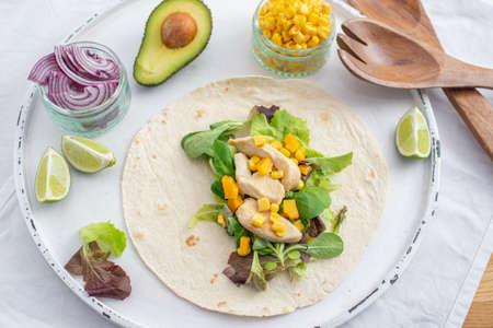 Fresh tortilla wraps with chicken, mushrooms and fresh vegetables on wooden board