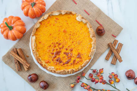 Slice of pumpkin pie on plate with pumpkins