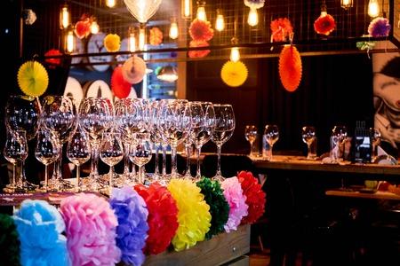 Festliche Bardekoration mit leeren Gläsern und künstlichen Blumen Standard-Bild - 80974056