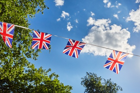 British Union Jack bunting flags against blue sky and green trees