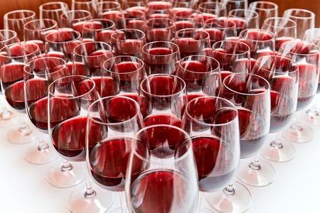 Gläser mit Rotwein auf einem weißen Tisch stehen in Form eines Dreiecks Standard-Bild - 89290530