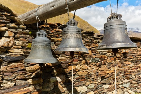 old bells in a mountain monastery on the background of mountains and stone walls in Georia Standard-Bild - 108151651