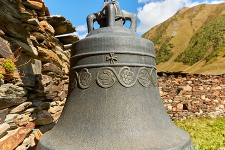 old bell in a mountain monastery on the background of mountains and stone walls in Georgia Standard-Bild - 108071619