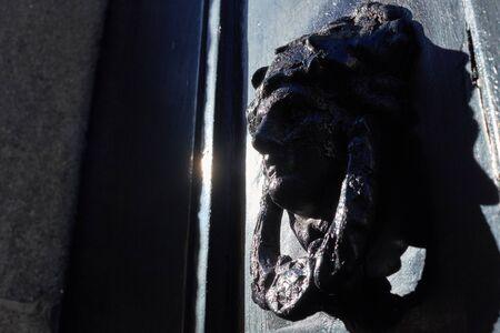 door knocker in the form of a head on a black door Standard-Bild