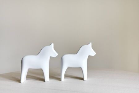 two ceramic horse figurines stand on a bright table Stock Photo