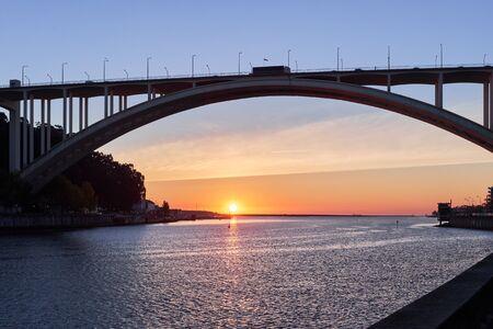 Arched bridge high above the strait sunset sun Standard-Bild