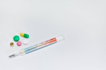 packaging with medicines and pills thermometer lie on a white background